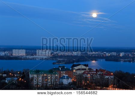 View of early moon in blue evening sky with reflection in the river. Cityscape
