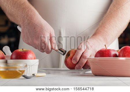 Chef Hands Removing Pit Of Freshly Peeled Apple Using A Paring Knife. Baking Apples Recipe Step