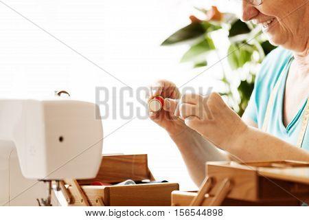 Senior woman sewing at home. Hobby time.