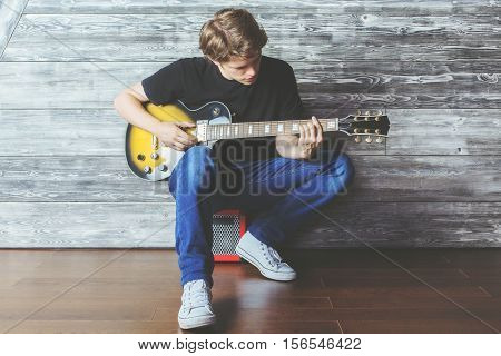 Handsome young boy with electric guitar sitting on amplifier in wooden room. Music concert rehearsal concept