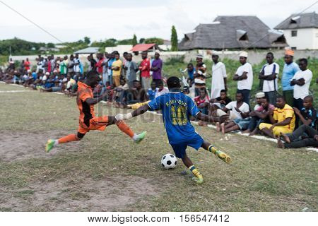 Zanzibar, Tanzania - July, 14, 2016: young african boys playing football on local Zanzibar field with viewers around