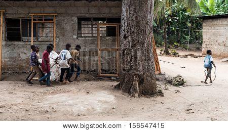 Zanzibar, Tanzania - July, 14, 2016: Editorial use - group of little african boys dragging together a sack on Zanzibar village street