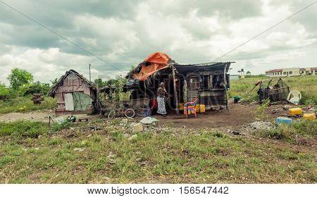 Zanzibar, Tanzania - July, 14, 2016: Editorial use - poor african hut in Zanzibar field with smiling woman and trash around