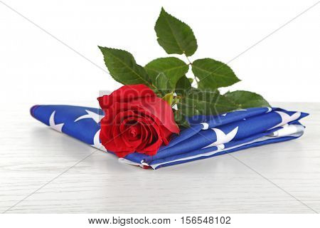 Red rose on American flag, isolated on white