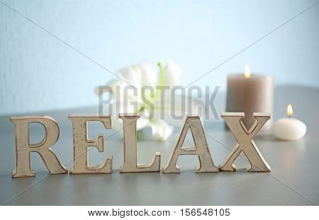 Word RELAX made of wooden letters with flower and candles on table