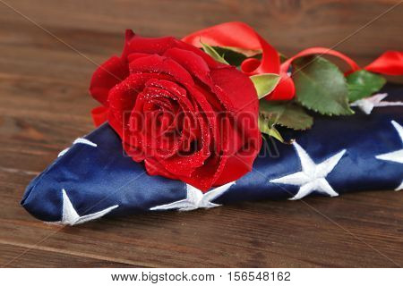 Red rose on American flag, closeup
