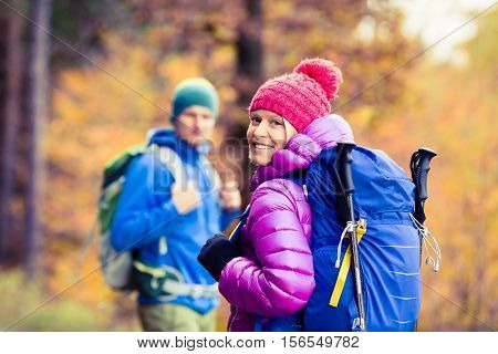 Man and woman happy couple hikers trekking in yellow autumn woods and mountains. Young people walking on trek trail with backpacks healthy lifestyle adventure camping on hiking trip Poland.