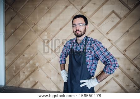 Young carpenter wearing gloves and glasses with hands on hips.