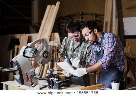 angry boss and worker together in a carpenter's workshop.