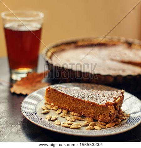 Piece of homemade pumkin pie closeup with pumkin seeds and tea. Thanksgiving traditional dessert. Selective focus