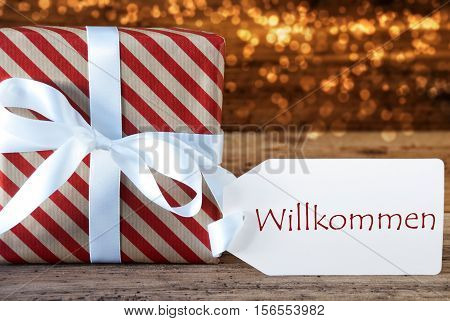 Macro Of Christmas Gift Or Present On Atmospheric Wooden Background. Card For Seasons Greetings, Best Wishes Or Congratulations. White Ribbon With Bow. German Text Willkommen Means Welcome