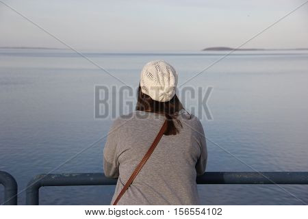 A young woman looks out at Lake Michigan, in Traverse City, Michigan