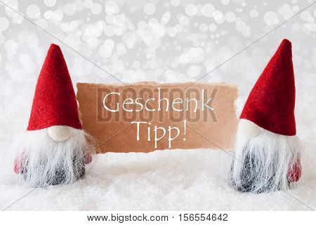 German Text Geschenk Tipp Means Gift Tip. Christmas Greeting Card With Two Red Gnomes. Sparkling Bokeh Background With Snow. English Text Seasons Greetings