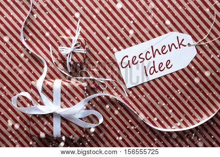 Label With German Text Geschenk Idee Means Gift Idea. Two Gifts Or Presents With White Ribbon. Red And Brown Striped Wrapping Paper. Christmas Or Greeting Card With Snowflakes.