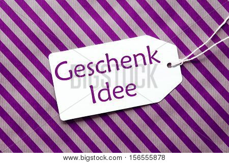 German Text Geschenk Idee Means Gift Idea. One Label On A Purple Striped Wrapping Paper. Textured Background. Tag With Ribbon.
