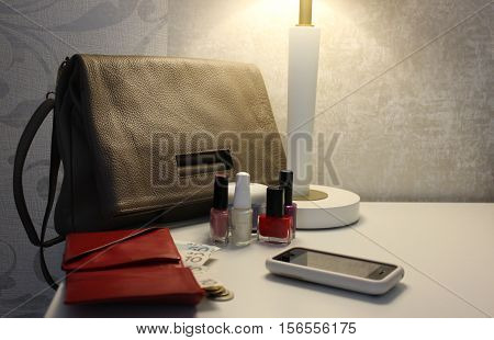 Female bag, open wallet with money, smartphone and nail polish on side table. Leather bag and wallet with phone on white table under the lamp.
