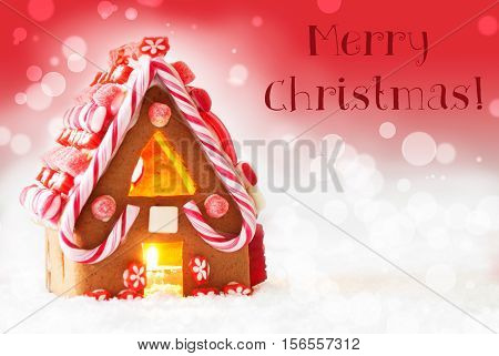 Gingerbread House In Snowy Scenery As Christmas Decoration. Candlelight For Romantic Atmosphere. Red Background With Bokeh Effect. English Text Merry Christmas