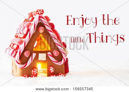 Gingerbread House In Snowy Scenery As Christmas Decoration With White Background. Candlelight For Romantic Atmosphere. English Quote Enjoy The Little Things