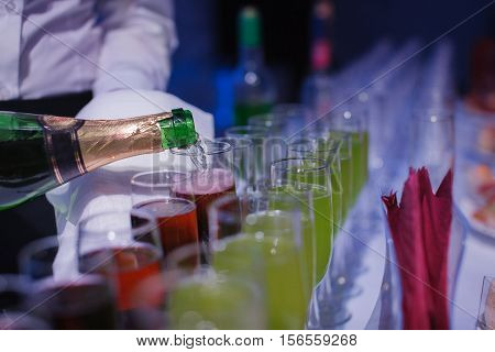 Champagne. being pored into glasses. banquet table. blue light