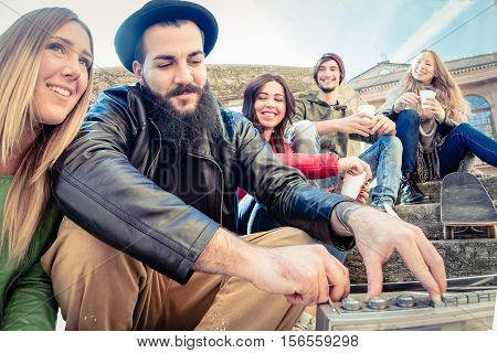 young hipster friends chilling outdoors sitting on ground drinking and listening to music having fun. happy carefree youth hanging out on a holiday enjoying company freedom laughing and talking