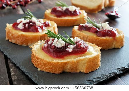Holiday Crostini Appetizers With Cranberry Sauce, Brie, Feta And Rosemary On A Slate Server