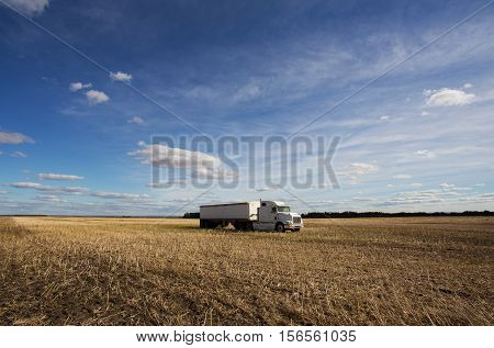 One white semi truck and trailer parked in a harvested field under dotted cloudy afternoon sky