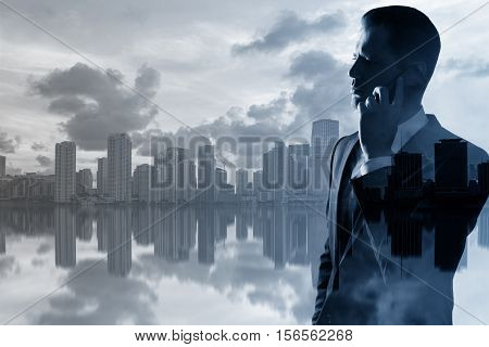 Backlit side portrait of handsome young businessman talking on mobile phone on creative city background with copy space. Double exposure. Communication concept