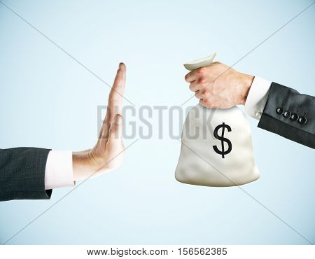 Hand saying no to money bag on light background. Stop corruption concept