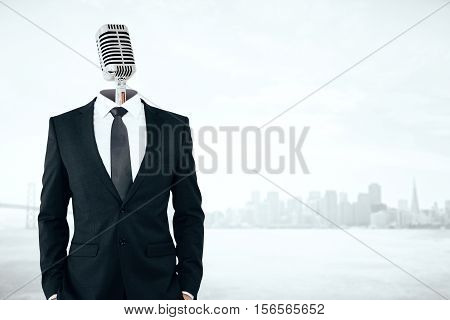 Mic headed businessman on city background with copy space. Voice concept