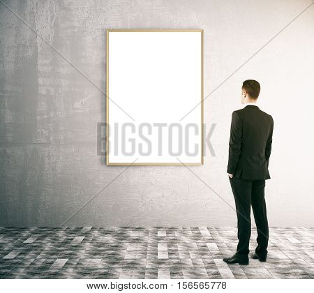 Back view of businessman looking at blank picture frame in interior with concrete wall and patterned floor. Mock up 3D Rendering
