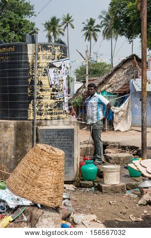 Dindigul India - October 23 2013: A Tamil man fills his colorful plastic jars with water out of large black communal water tank. Surrounded by garbage a basket and junk. Street scene. Green foliage.