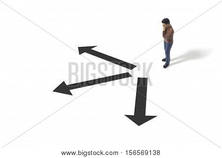 Toy Person Standing Next to Various Direction Arrows on the Ground