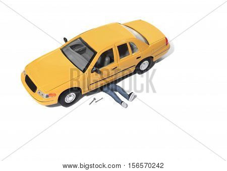 Still life of a Toy Person Working Under a Model Car on White Background
