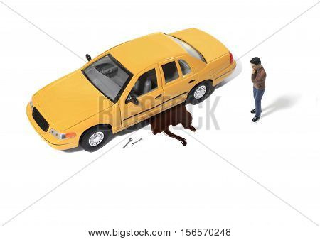 Toy Man looking at Oil Leaking from Car on White Background