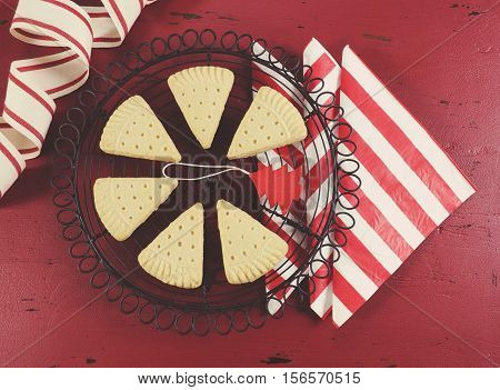 Christmas Shortbread Triangle Cookies On Vintage Baking Rack On Dark Red Rustic Wood Background With