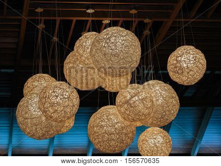 Modern,stylish electrical lanterns spheres hanging out from brown ceiling on dark blue attic interior roof background