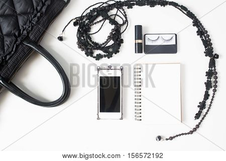Flat lay of empty notebook cellphone and woman's accessories in black concept top view isolated on white background