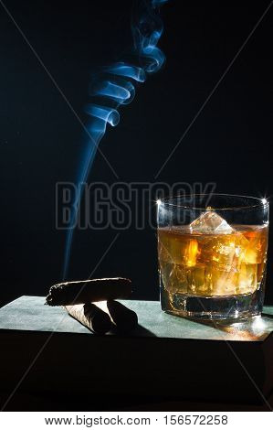 Strange Blue Smoke Moving Up From Cigar And Whisky In Glass