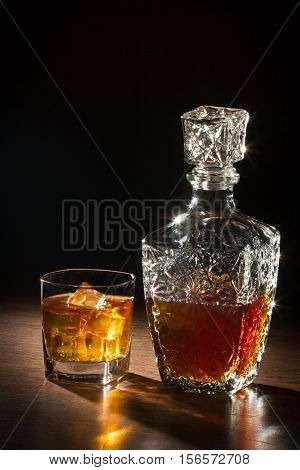 Whisky on ice and glass carafer on wooden table