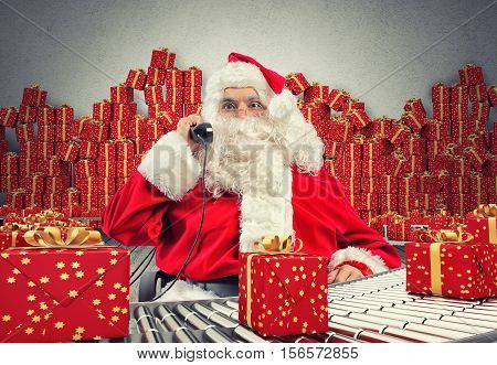 3D Rendering Santa Claus receives requests via telephone sitting in a chair and checking xmas gift boxes and wrapped on conveyor roller