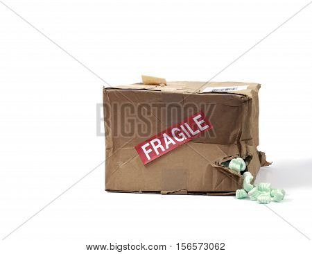 Still Life of a Beat Up Cardboard Delivery Box with Styrofoam Peanuts Spilling Out on White Background