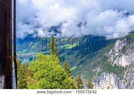 View of beautiful landscape in the Alps with fresh green meadows and snow-capped mountain tops in the background on clouds in springtime.