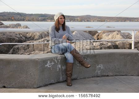 A young woman sits on the breakwater in Traverse City, Michigan