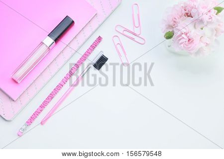 A white table top mock up of a desk with a pink notebook, paper clips, pencil, lipstick and miniature pink carnation flowers.