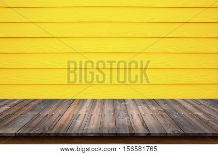 Empty top of wood table with yellow wood wall background. For display or montage your products.