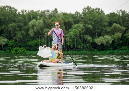 cheerful happy couple woman and man on the stand up paddle with gifts, white bags and copy space