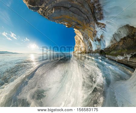 Ice grotto in rock on Olkhon Island on Lake Baikal ice covered wide-angle panorama.