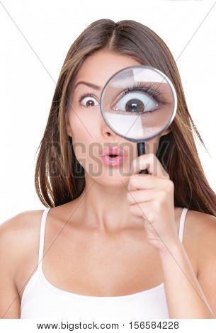 Shocked woman looking through a magnifying glass. Funny surprised Asian girl astonished discovering clues through a magnifying glass, isolated on white background. Big eye closeup.