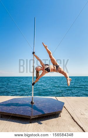 Female pole dancer against the sea and sky