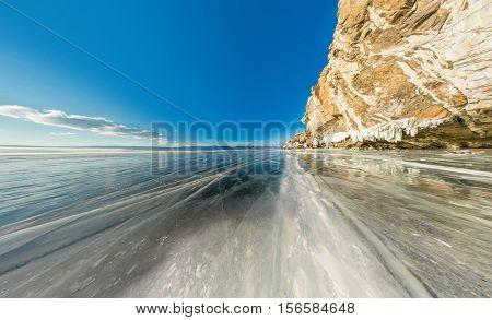 Rock on Olkhon Island on Lake Baikal ice covered wide-angle panorama.